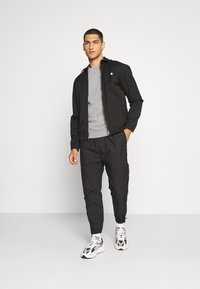 Weekday - ASTON ZIPPED TROUSERS - Trousers - black