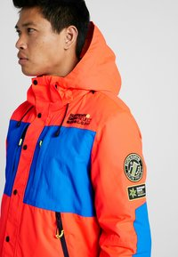 Superdry - MOUNTAIN JACKET - Laskettelutakki - hazard orange/acid cobalt - 9