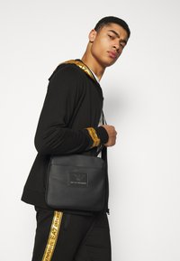 EA7 Emporio Armani - Zip-up hoodie - black/gold - 3