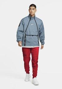 Nike Sportswear - FLEECEBYXOR - Tracksuit bottoms - black university red white - 1