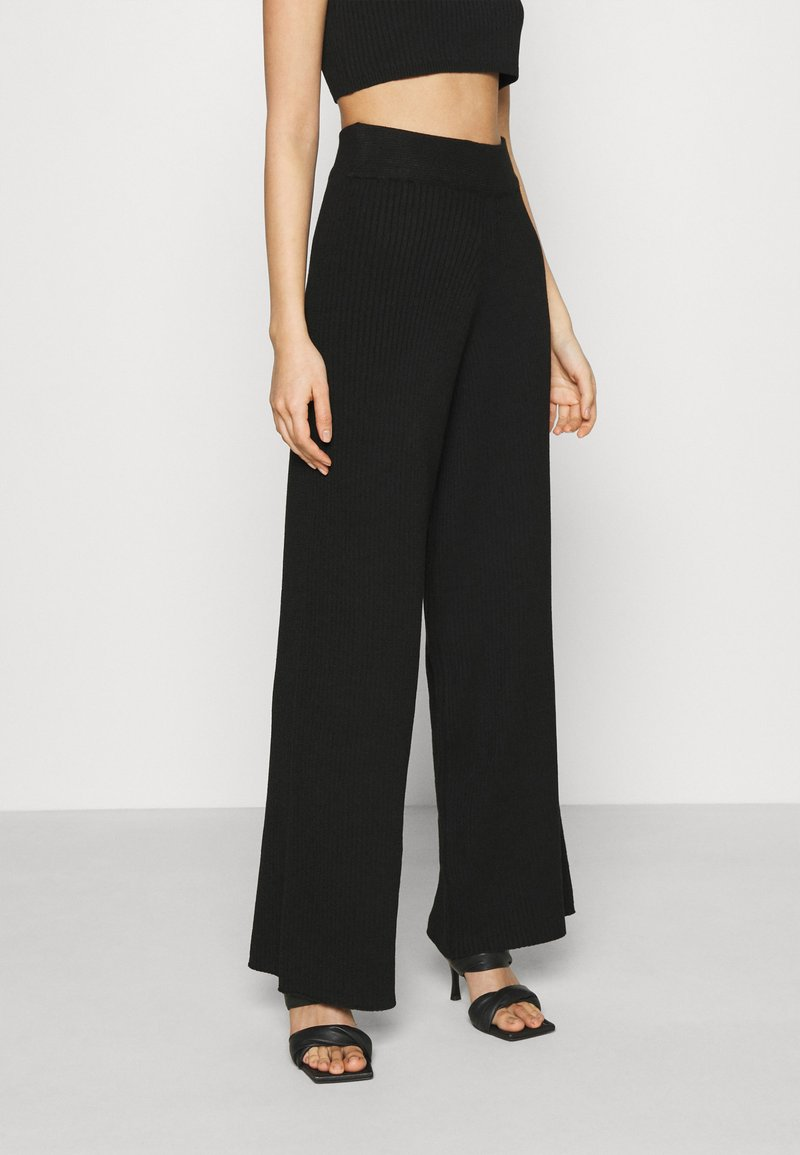 NA-KD - NA-KD X ZALANDO EXCLUSIVE SOFT RIBBED PANTS - Trousers - black