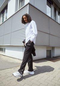 Pegador - VINTO WIDE TRACK PANTS UNISEX - Tracksuit bottoms - black - 1