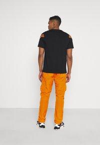Karl Kani - SIGNATURE CRINCLE PANTS UNISEX - Pantalon cargo - orange - 2