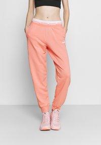 Puma - AMPLIFIED PANTS - Tracksuit bottoms - apricot blush - 0