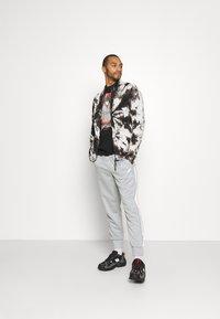 Nike Sportswear - REPEAT - Träningsbyxor - light smoke grey/white - 1