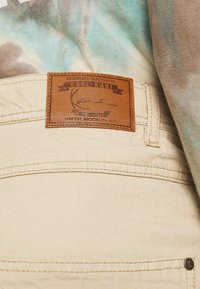 Karl Kani - RINSE BLOCK PANTS - Relaxed fit jeans - beige - 5
