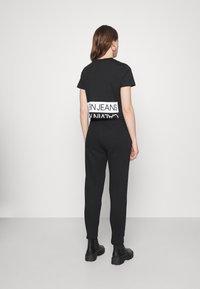 Calvin Klein Jeans - SHINY RAISED PANT - Tracksuit bottoms - black - 2