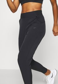 Nike Performance - BLISS - Tracksuit bottoms - black - 3