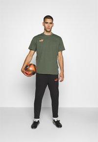 Puma - CASUALS PANT - Pantalon de survêtement - black/fizzy orange - 1