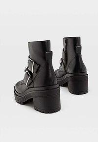 Stradivarius - MIT PROFIL, UND DEKORATIVER KET - Cowboy/biker ankle boot - black - 3