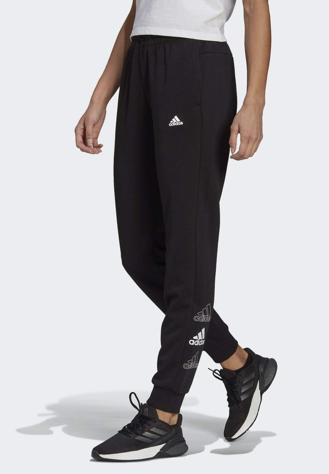 ADIDAS ESSENTIALS STACKED LOGO JOGGERS - Tracksuit bottoms - black