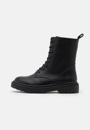 VEGAN FREDA COMBAT LACE UP BOOT - Platform ankle boots - black
