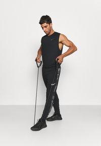 Nike Performance - CAMO - Tracksuit bottoms - black/white - 1