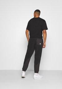adidas Originals - UNISEX - Tracksuit bottoms - black - 2