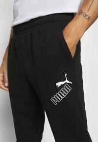 Puma - AMPLIFIED PANTS - Pantalon de survêtement - black - 5