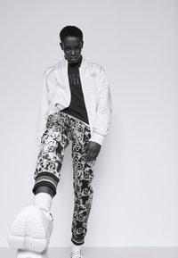 Versace Jeans Couture - TECNO  PRINT LOGO BAROQU  - Tracksuit bottoms - black - 3