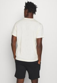 Champion - LEGACY HERITAGE TECH SHORT SLEEVE - T-shirt imprimé - offwhite/black - 2
