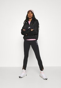 Nike Sportswear - LEGASEE ZIP - Leggings - black/white