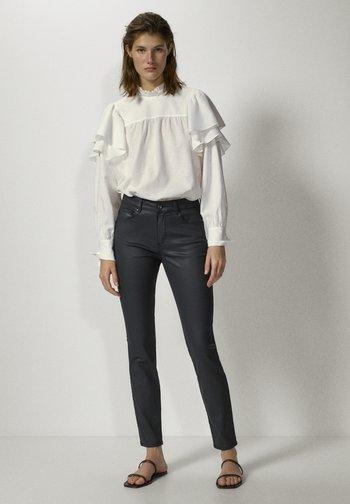 MIT GUMMIERTEM FINISH - Jeans Skinny - black