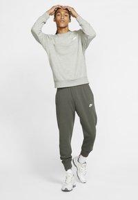 Nike Sportswear - CLUB - Tracksuit bottoms - twilight marsh/twilight marsh/white - 1