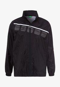 Erima - Regenjacke / wasserabweisende Jacke - schwarz / weiß - 0