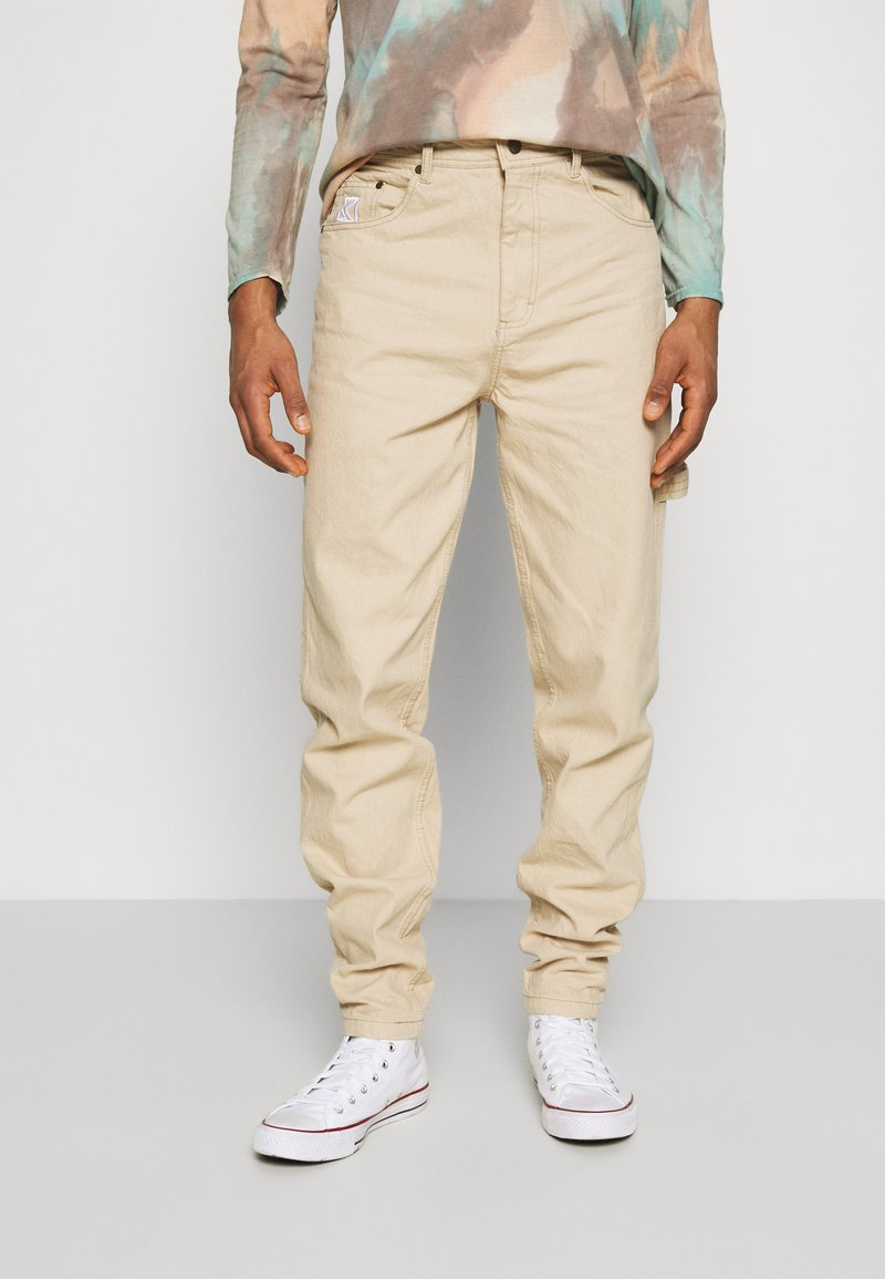Karl Kani - RINSE BLOCK PANTS - Relaxed fit jeans - beige