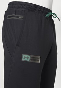 Under Armour - STORM PANTS - Tracksuit bottoms - black