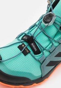 adidas Performance - TERREX MID GTX UNISEX - Hiking shoes - acid mint/core black/screaming orange - 5