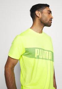Puma - TRAIN GRAPHIC SHORT SLEEVE TEE - T-shirt print - fizzy yellow - 3