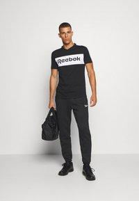 Reebok - CUFFED PANT - Pantalon de survêtement - black - 1