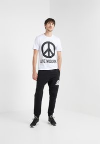 Love Moschino - Tracksuit bottoms - black - 1