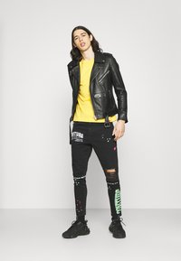 The Couture Club - NEON GRAFITTI CARROT FIT JEANS - Jeans slim fit - washed black - 1
