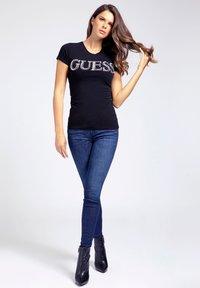 Guess - APPLIKATIONEN - T-shirt z nadrukiem - schwarz - 1