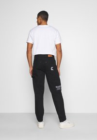 Karl Kani - RINSE PANTS - Relaxed fit jeans - black