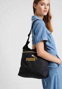 Puma - CORE SEASONAL SHOPPER - Tote bag - black/gold - 1