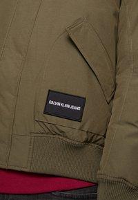 Calvin Klein Jeans - FUR TRIMMED HOODED DOWN BOMBER - Down jacket - dark green - 7