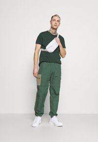 adidas Originals - UTILITY TWO IN ONE ORIGINALS - Cargo trousers - green oxide/clay - 1