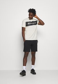 Champion - LEGACY HERITAGE TECH SHORT SLEEVE - T-shirt imprimé - offwhite/black - 1