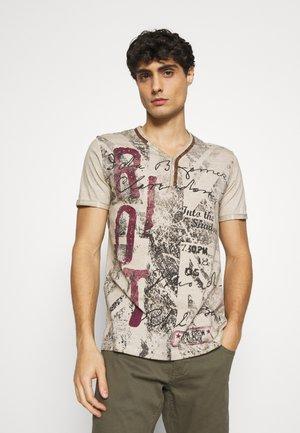 RIOT BUTTON - T-shirt med print - sand