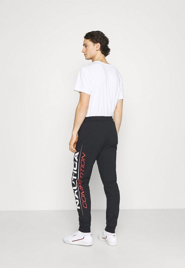 PINISI - Teplákové kalhoty - black