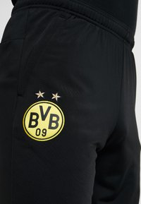 Puma - BVB BORUSSIA DORTMUND TRAINING PANTS WITH ZIP POCKETS - Tracksuit bottoms - black/cyber yellow - 6