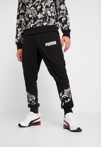 Puma - REBEL CAMO PANTS - Pantalon de survêtement - black - 0