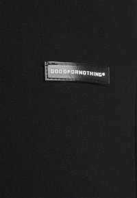 Good For Nothing - ESSENTIAL JOGGER WITH RUBBER BADGE - Tracksuit bottoms - black - 5