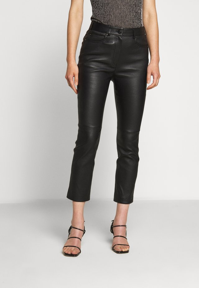 LAKKILI - Leather trousers - black