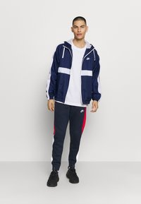Nike Sportswear - Tracksuit bottoms - obsidian/university red/white - 1
