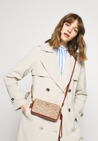 Coach - COLORBLOCK COATED SIGNATURE KIRA CROSSBODY - Umhängetasche - tan rust