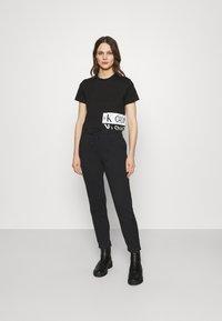 Calvin Klein Jeans - SHINY RAISED PANT - Tracksuit bottoms - black - 1