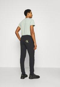 Calvin Klein Jeans - MONOGRAM - Tracksuit bottoms - black - 2