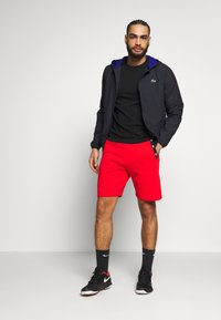 Lacoste Sport - SHORT TAPERED - Sports shorts - corrida/black - 1