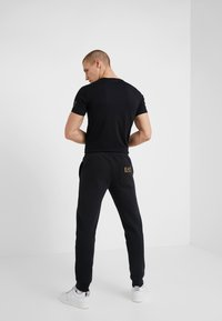 EA7 Emporio Armani - PANTALONI - Pantaloni sportivi - black/gold - 2